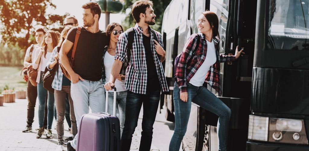 Gruppenreisen Personen mit Koffern am Bus